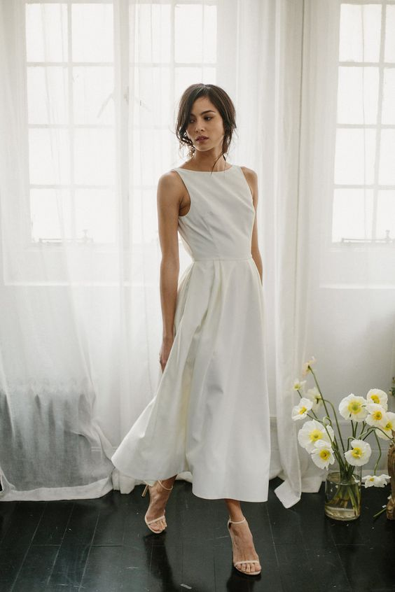 a modern plain sleeveless tea length wedding dress with a pleated skirt, nude shoes for a simple and laconic look