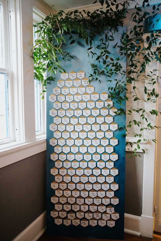 a modern seating chart with gilded hexagons and lush greenery for decor will fit not only a fall wedding