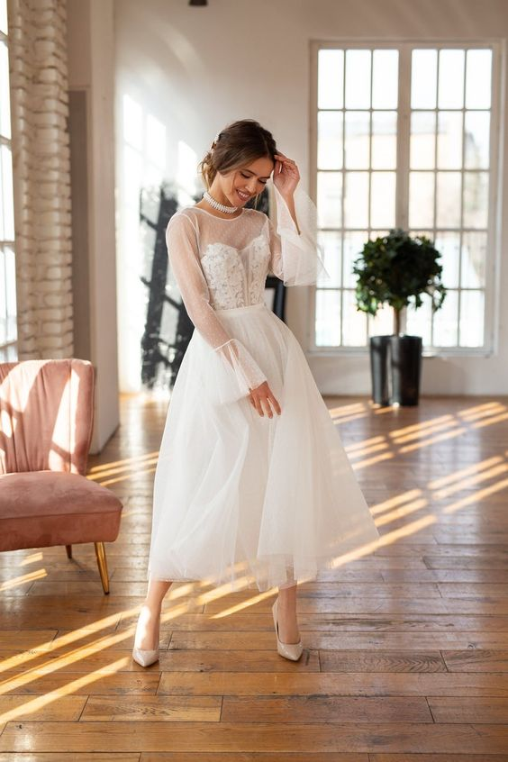 a modern take on a vintage tea length wedding dress with an illusion neckline, illusion sleeves and a layered skirt plus nude shoes