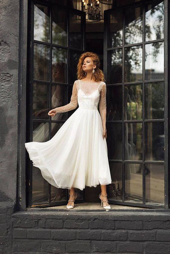a modern tea length wedding dress with an illusion bodice and a pelated skirt plus spiked shoes for a modern bride