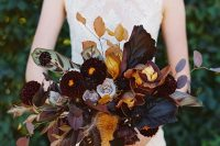 a moody and luxurious fall wedding bouquet with dark leaves, blooms, touches of mustard and rust, dried leaves and some herbs