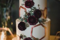a moody fall wedding cake with copper hexagons and greenery and purple blooms looks amazing