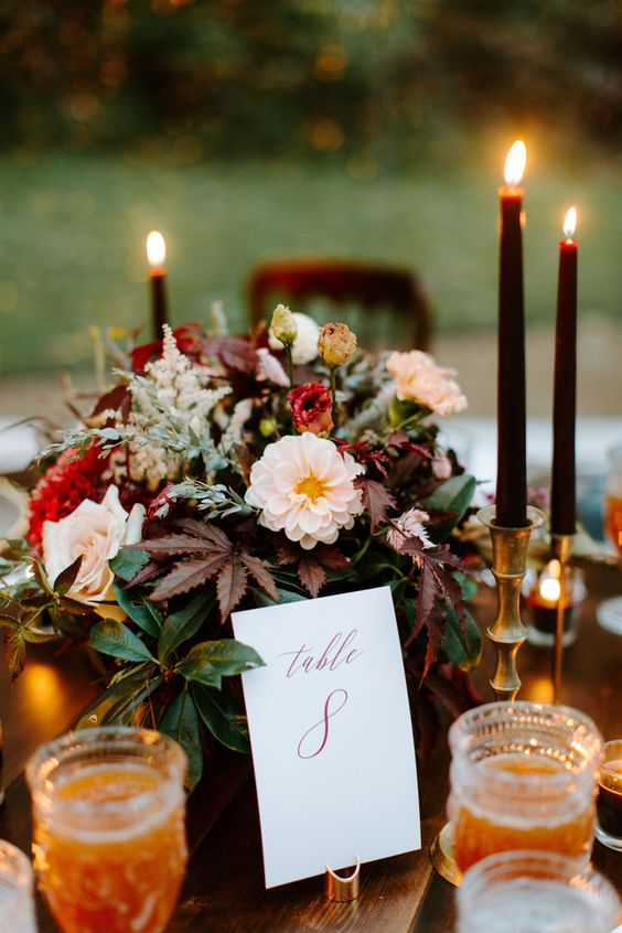 a moody fall wedding centerpiece of red and blush blooms, foliage and herbs and black candles