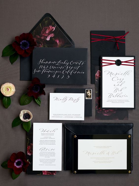 a moody invitation suite with black envelopes and moody floral lining plus white invites