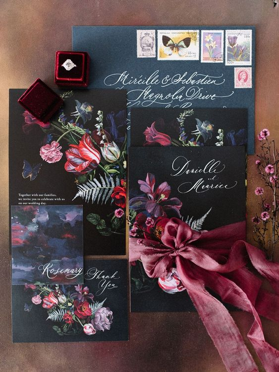 a moody wedding invitation suite in black, grpahite grey and with bold florals and a pink ribbon bow