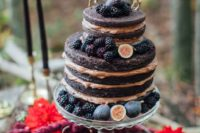 a naked chocolate fall wedding cake topped with blackberries, figs and gilded deer toppers