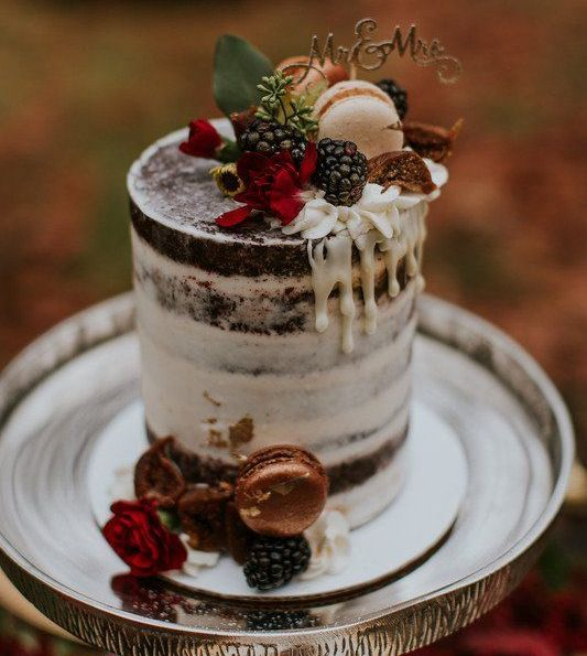 a naked chocolate fall wedding cake topped with blackberries, metallic macarons, blooms and a delicate monogram topper