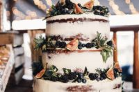 a naked fall wedding cake decorated with blackberries, blueberries, thistles and figs for a fall wedding