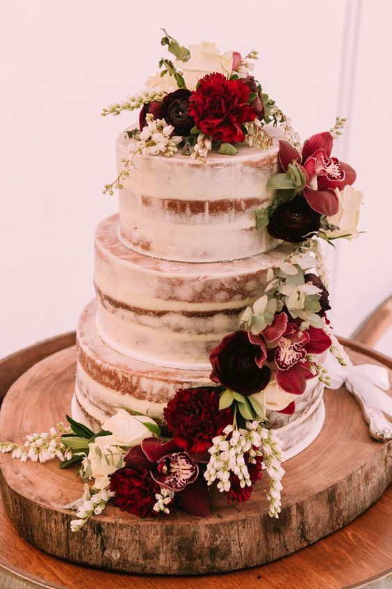 a naked wedding cake decorated with burgundy and white blooms and foliage for a brighter look