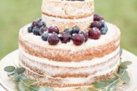 a naked wedding cake topped with fresh berries and foliage is a simple and laconic fall idea