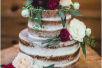 a naked wedding cake topped with neutral and bold blooms and some greenery is a popular idea for the fall