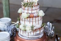 a naked wedding cake with copper drip, greenery and white blooms plus copper macarons