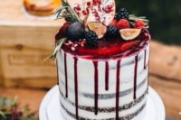 a naked wedding cake with cranberry drip and fresh fruits on top the cake