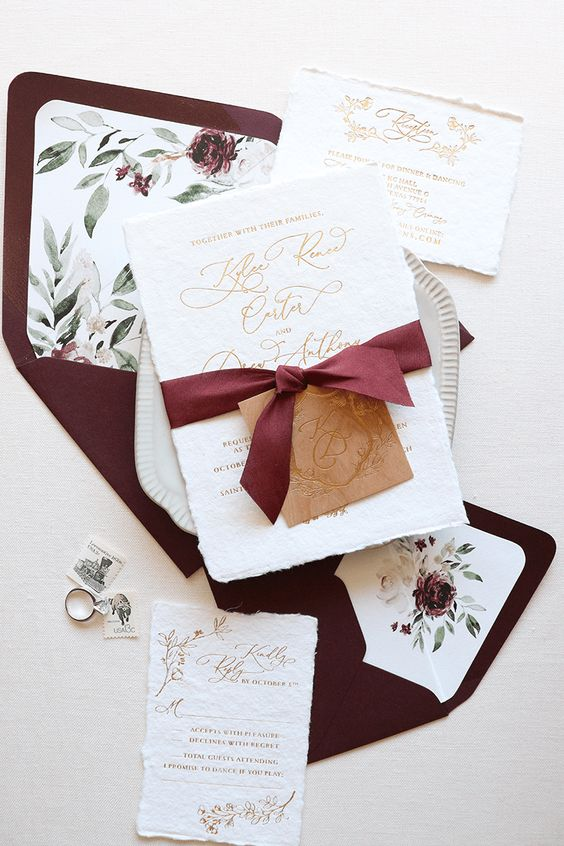 a neutral and gold wedding invitation suite with bold burgundy envelopes with a floral lining