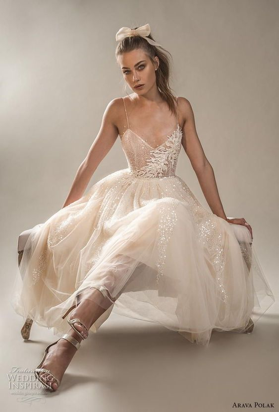 a neutral embellished wedding dress with lace appliques, a deep V-neckline, spaghetti straps and silver shoes for a modern glam bride
