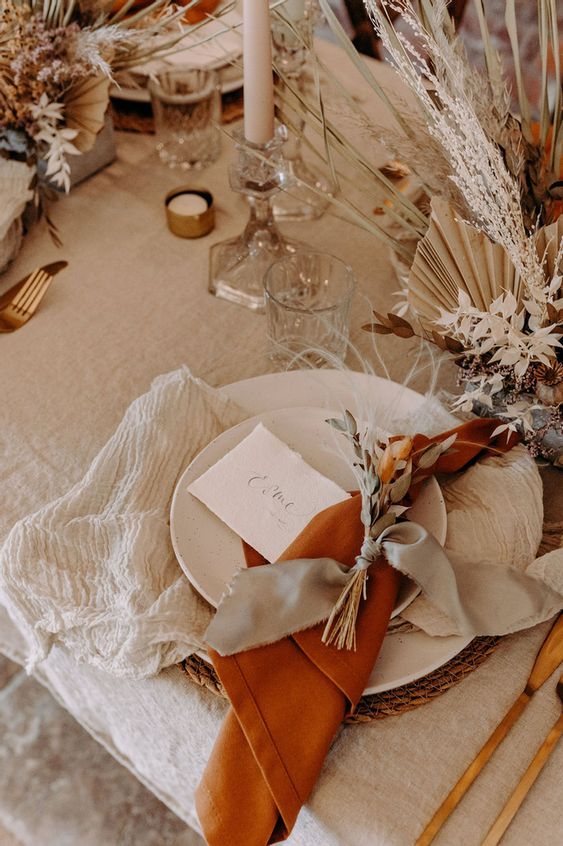 a neutral fall wedding table setting with white plates, jute placemats, neutral and orange napkins, dried blooms, leaves and fronds and candles