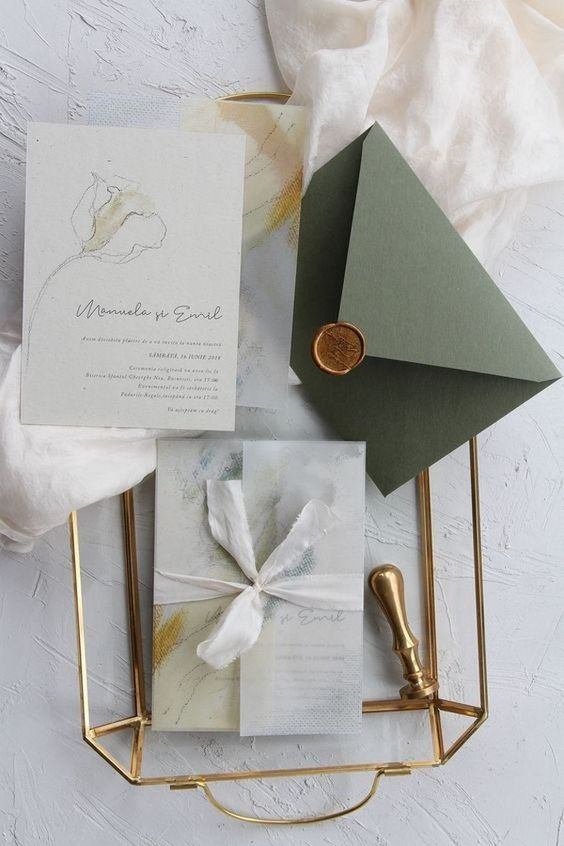 a neutral wedding invitation suite with marbleized invites and an olive green envelope with a seal