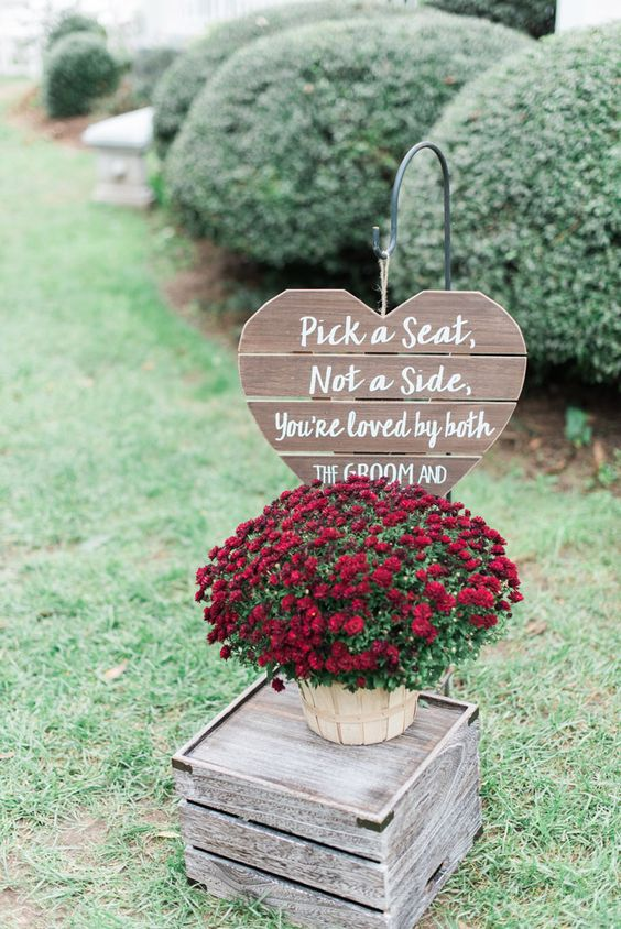 a pallet heart sign, a wooden basket with burgundy blooms on a crate for decorating an outdoor fall wedding space