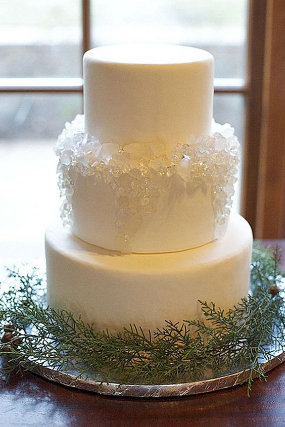 a plain white wedding cake decorated with white sugar rocks is gorgeous for a modern wedding