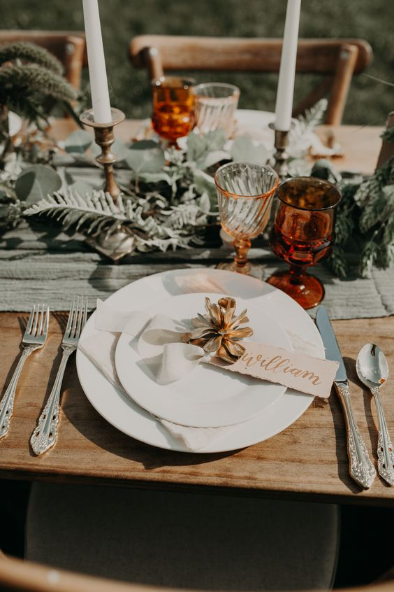 a pretty and catchy fall wedding tablescape with an olive green table runner, neutral porcelain, elegant cutlery, greenery, amber glasses and tall candles