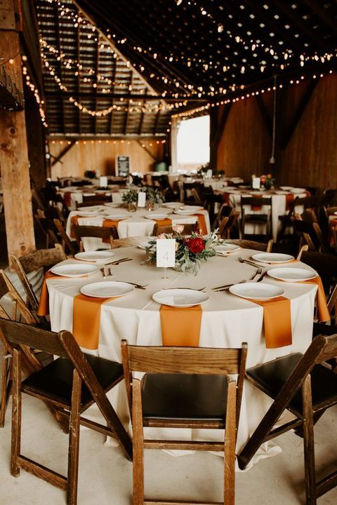 a pretty and simple rustic fall wedding tablescape with orange napkins, colorful blooms and greenery and a white tablecloth is cool