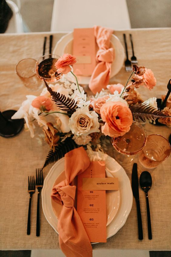 a pretty modern wedding tablescape with a rust, blush and orange floral centerpiece, rust napkins and menus, black cutlery