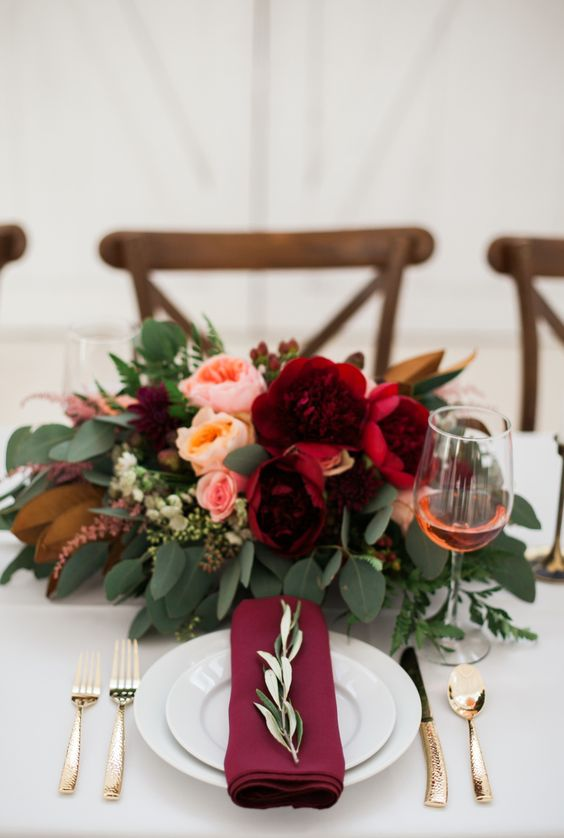a purple napkin and a bold floral centerpiece with greenery, blush and peachy blooms plus burgundy ones for a touch of color
