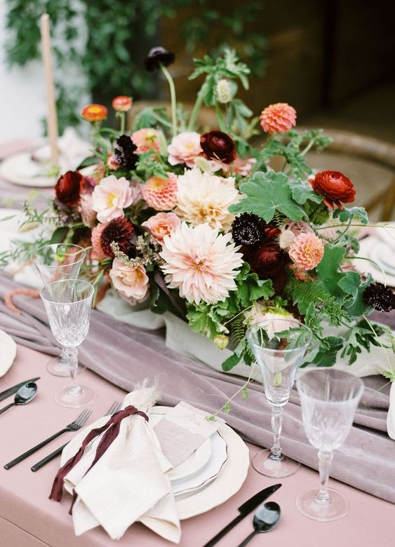 a refined autumn wedding centerpiece of leaves, blush, red and burgundy blooms is very elegant