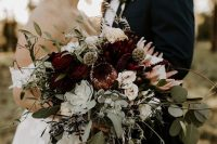 a refined fall wedding bouquet of white, burgundy and pink flowers, greenery, thistles, a succulent and berries is a classy idea for the fall