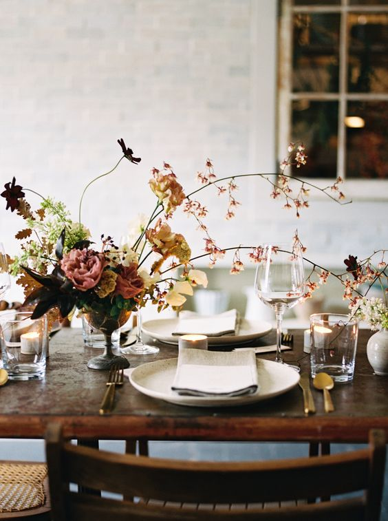 a refined fall wedding centerpiece of a bowl, greenery and foliage, blooming branches and dark blooms