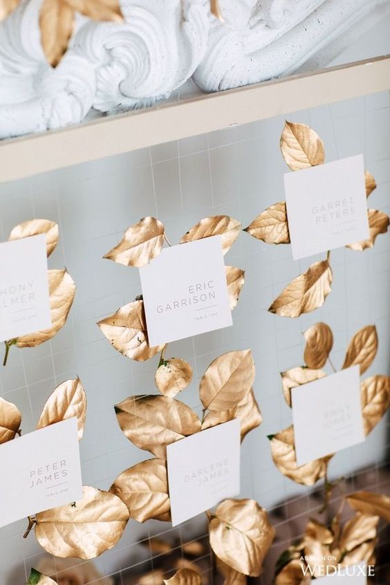 a refined fall wedding seating chart of net and gildede leaves and cards is a gorgeous idea
