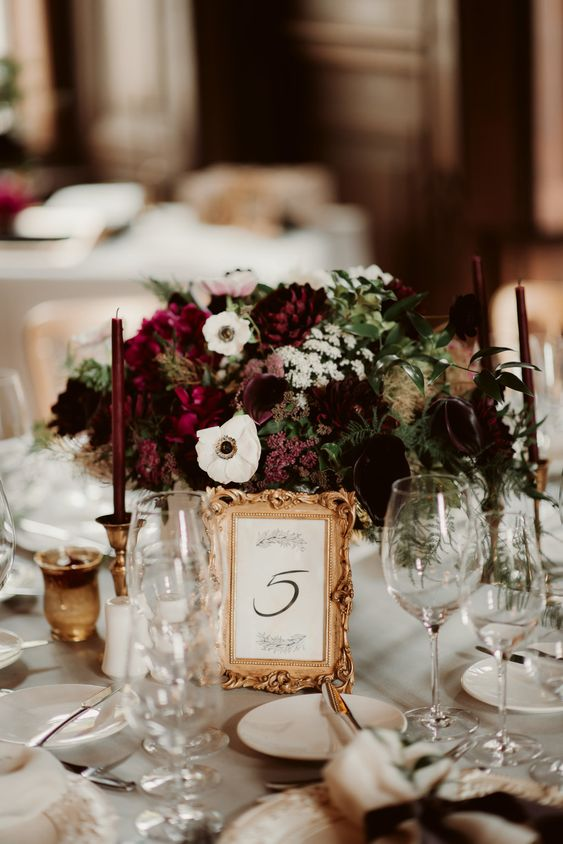 a refined moody floral centerpeice of purple, burgundy, white blooms and a chic framed table number