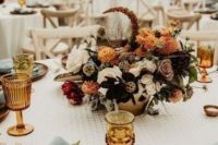 a refined wedding table setting with amber goblets, wooden plates, gold cutlery and rust and amber blooms