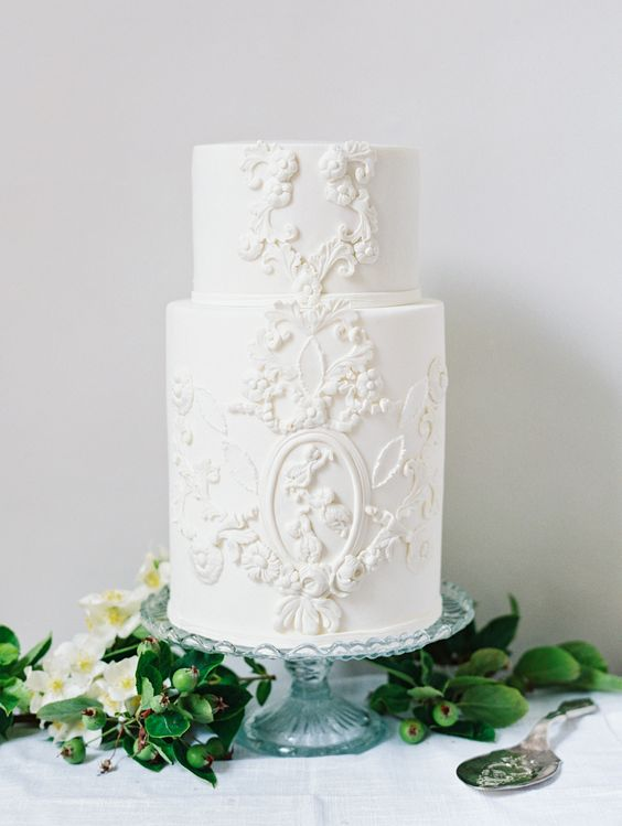 a refined white wedding cake with sugar patterns and blooms is perfect for a vintage wedding