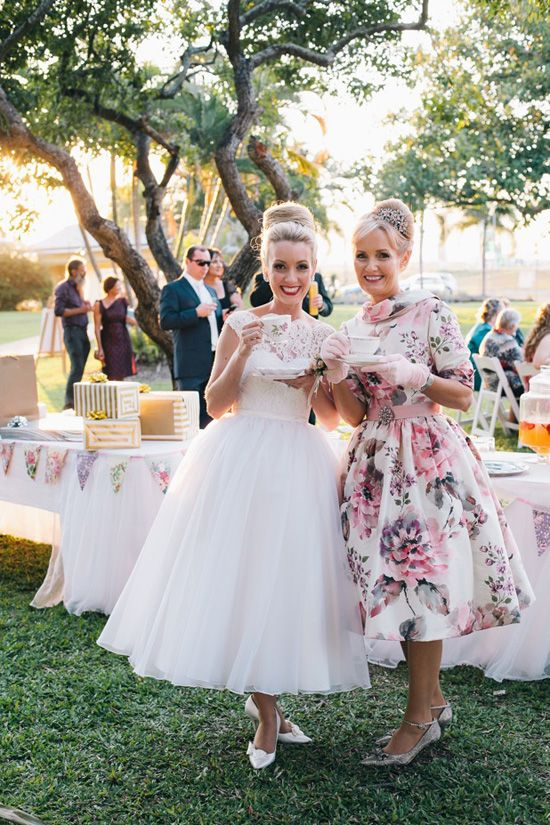 a retro tea length wedding dress with a lace bodice and a tulle layered skirt, white shoes and a top knot is wow