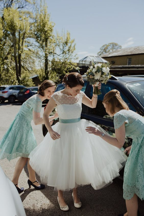 a retro tea length wedding dress with a polka dot bodice, a tulle layered skirt, white shoes, a mint green sash for a sweet look