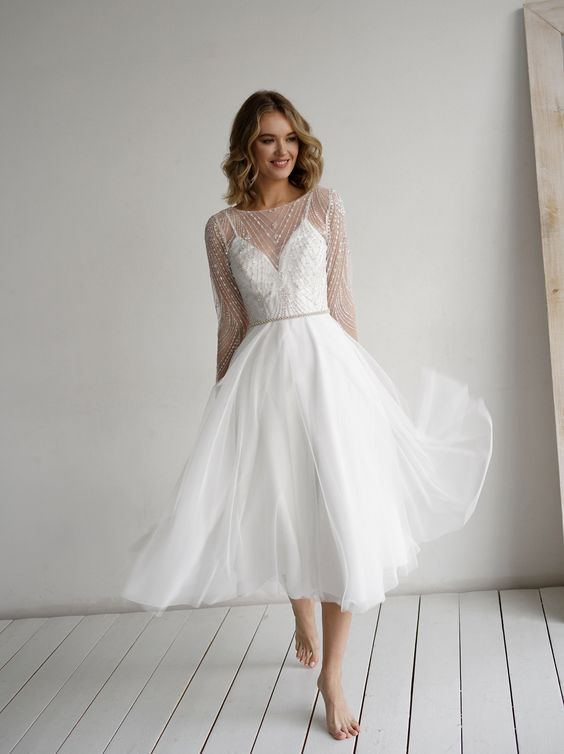 a retro tea length wedding dress with an embellished bodice, long sleeves and layered skirt