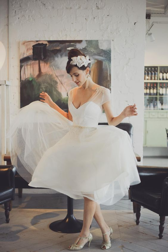 a retro tea length wedding dress with an illusion neckline, a tulle skirt, silver peep toe shoes and a vintage headpiece