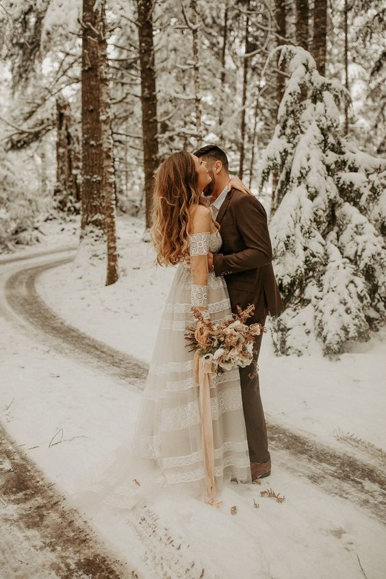 a romantic A-line off the shoulder wedding dress with lace inserts for a winter elopement in the woods