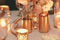 a romantic and glam wedding centerpiece of copper bottles and vases, blush blooms and copper candleholders