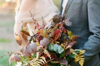 a romantic fall boho wedding bouquet with no blooms, only berries and foliage of all colors possible plus ribbons is amazing