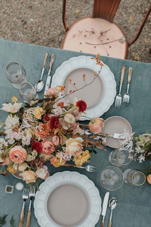 a romantic fall wedding centerpiece of muted color blooms and some branches with berries is a beautiful idea of an arrangement