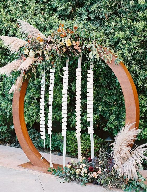 a round arch decorated with greenery, bright blooms and leaves and pampas grass and straps of fabric with cards