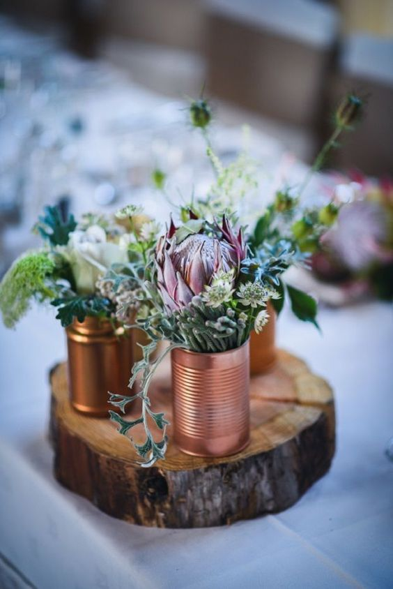 a rustic wedding centerpiece of a wood slice, copper and gold tin cans, greenery and neutral and pink blooms