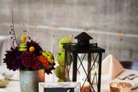 a rustic wedding centerpiece of moss, white pumpkins, moss balls, dark blooms and a candle lantern