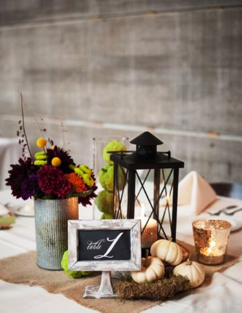 a rustic wedding centerpiece of moss, white pumpkins, moss balls, dark blooms and a candle lantern