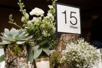 a rustic wedding centerpiece of tree stumps with white blooms, succulents, candles and a modern table number