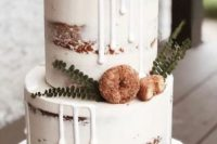a semi naked fall wedding cake decorated with white drip, greenery and donuts looks delicious