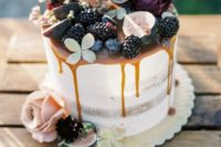 a semi naked fall wedding cake with caramel drizzle, blackberries, figs, blooms and succulents on top