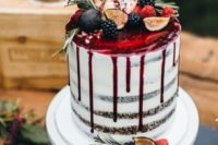 a semi naked wedding cake with pomegranate drizzle, blackberries and figs and some greenery on top